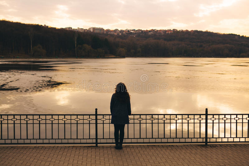 Lonely woman alone in winter at sunset stock photos