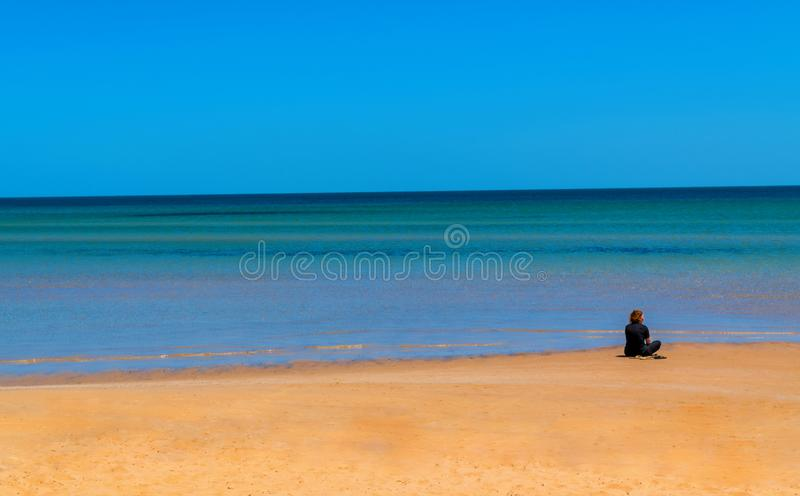 Lonely woman at the beach stock image