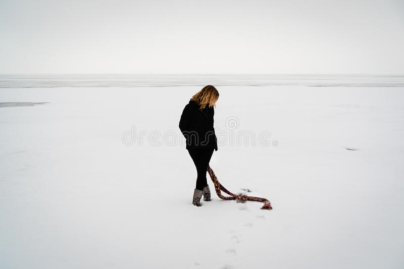 Lonely woman in dark clothing with a colored scarf walks through the snow-covered frozen sea against the horizon stock image