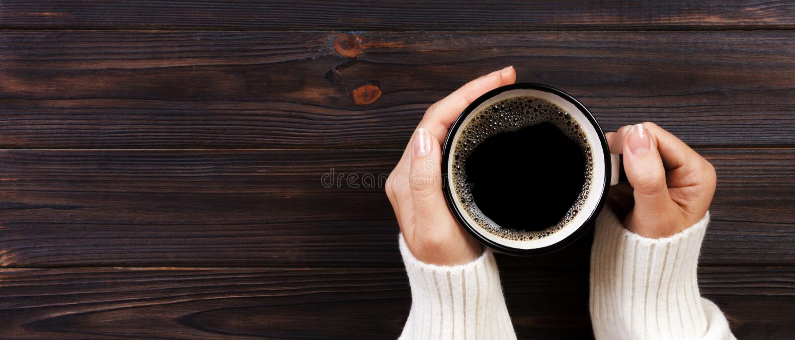 Lonely woman drinking coffee in the morning, top view of female hands holding cup of hot beverage on wooden desk. Banner royalty free stock image