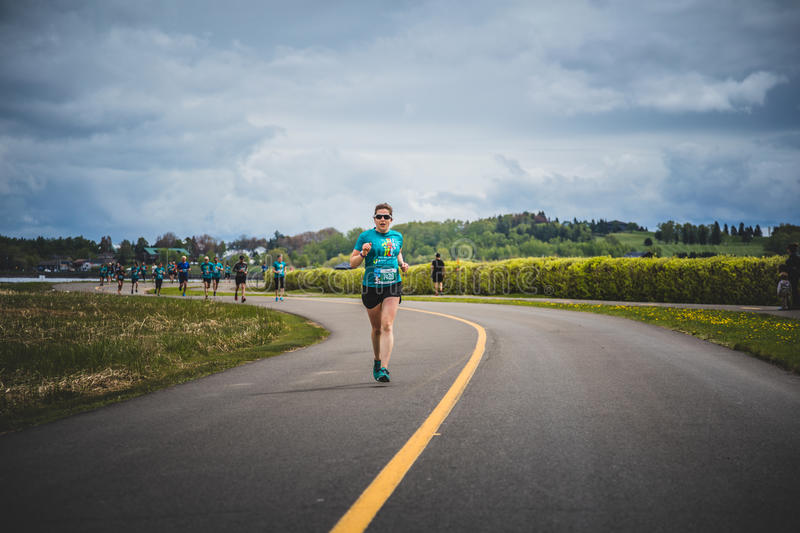 Lonely Woman Leading a Group of 10K Runners. CARLETON, CANADA - June 4, 2017. During the 5th Marathon of Carleton in Quebec, Canada. Lonely Woman Leading a Group stock photo