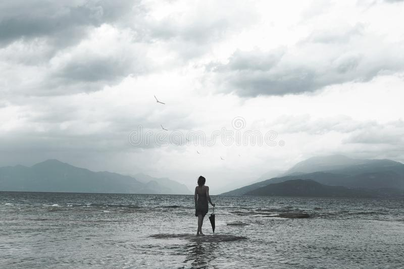 Lonely woman looks at infinity and uncontaminated nature on a stormy day. Solitary woman looks at infinity and uncontaminated nature on a stormy day stock image
