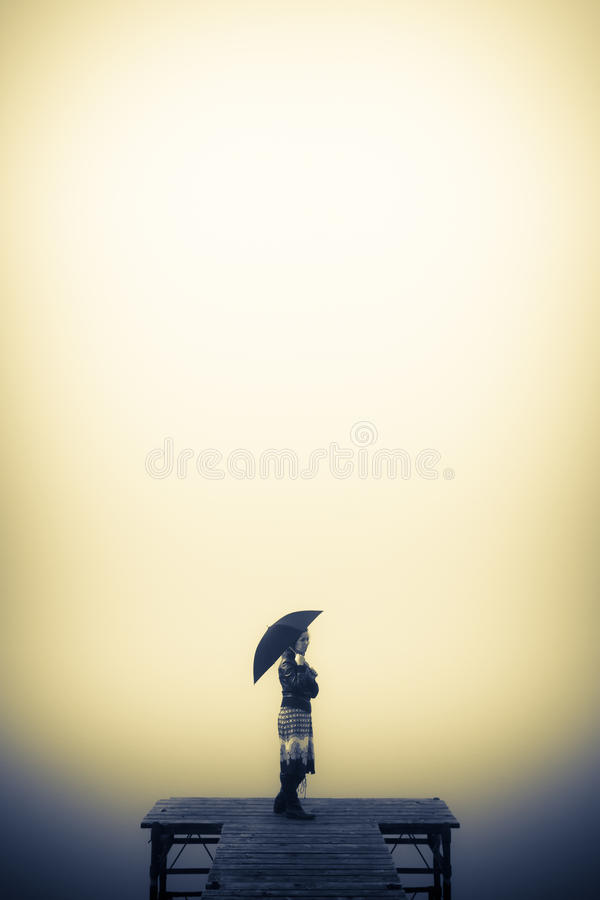 Lonely woman looks to the misty lake stock images