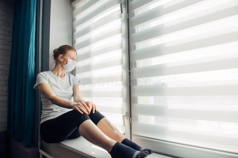 Lonely woman in protective medical mask on her face looking at window, copy space. Pandemic coronavirus, virus Covid-19. Quarantine, prevent infection, home stock photography