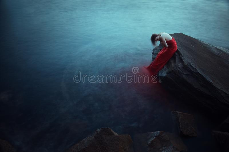 Lonely woman near the sea. Lonely woman in red dress near the sea royalty free stock image