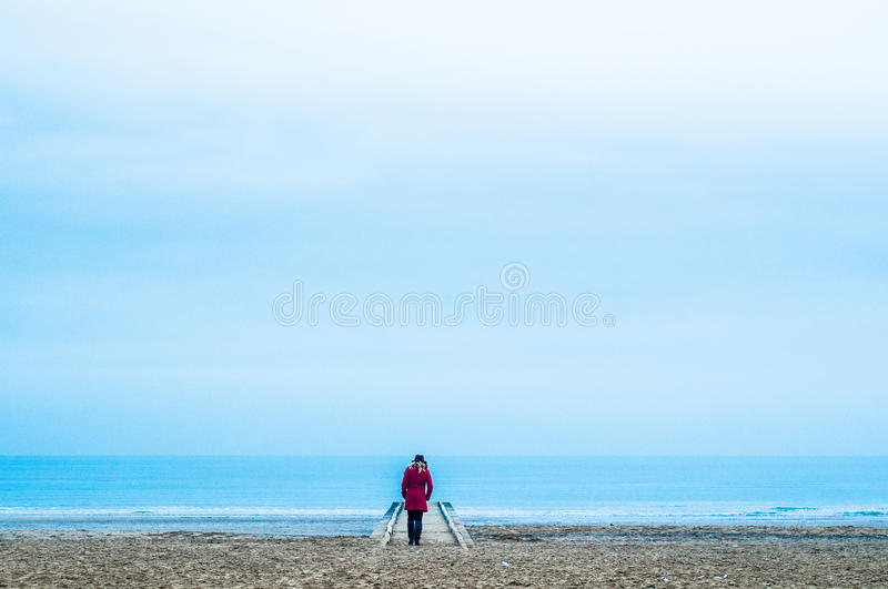Lonely woman in red dress in wooden pier at the beach with calm sea stock images