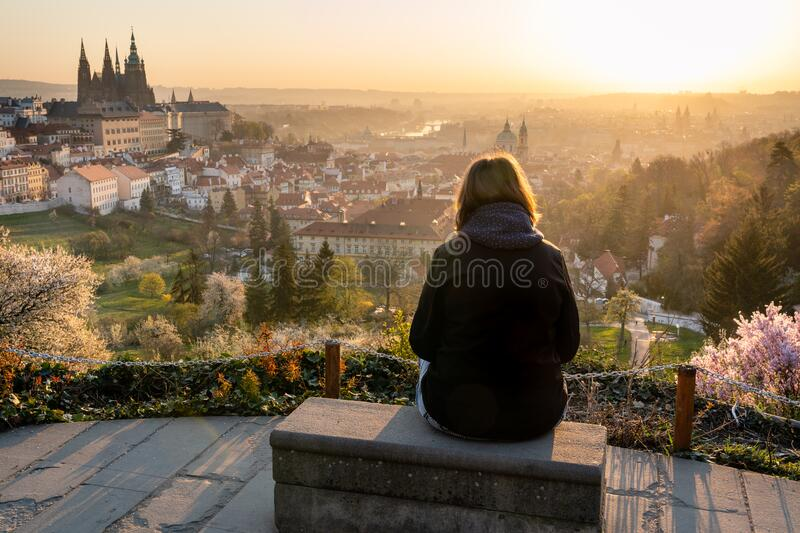 Lonely woman in 40s relaxing outside in city park and enjoying the view of Prague. Female sitting on a bench, looking at beautiful. Sunrise over old town stock photo