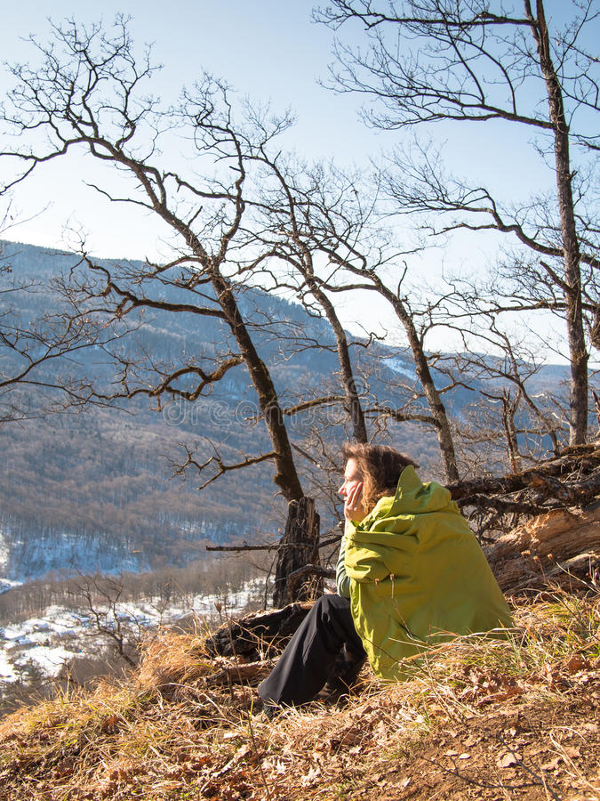 Lonely woman sitting on a hillside stock photography