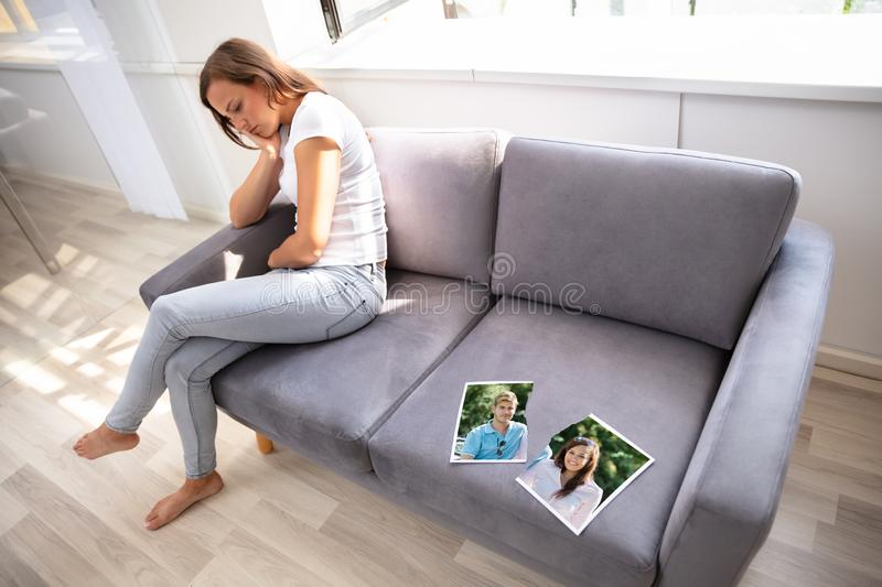 Lonely Woman Sitting On Sofa. With Torn Photograph royalty free stock photo
