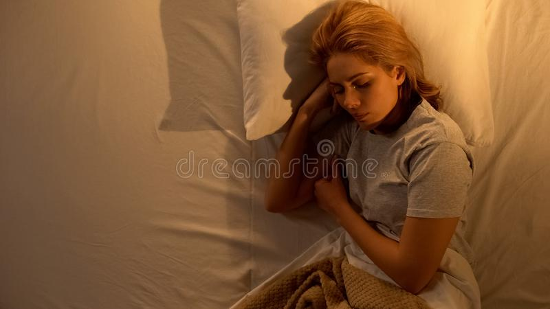 Lonely woman sleeping in big bed alone, break up with husband, betrayal problem. Stock photo royalty free stock image