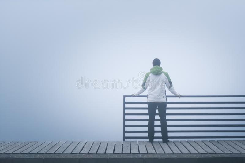 Lonely woman standing alone on the bridge, lost in thought on a foggy day stock photos