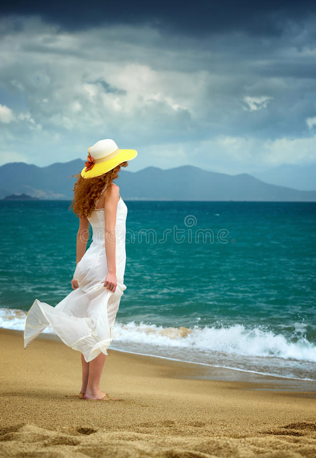 Lonely woman standing at the sea royalty free stock photo