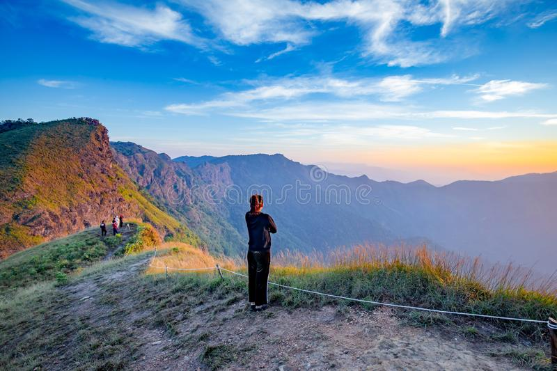 Lonely woman on top of the mountain with sunrise background royalty free stock photography