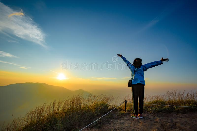 Lonely woman on top of the mountain with sunrise background stock photos