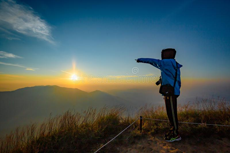 Lonely woman on top of the mountain with sunrise background stock images