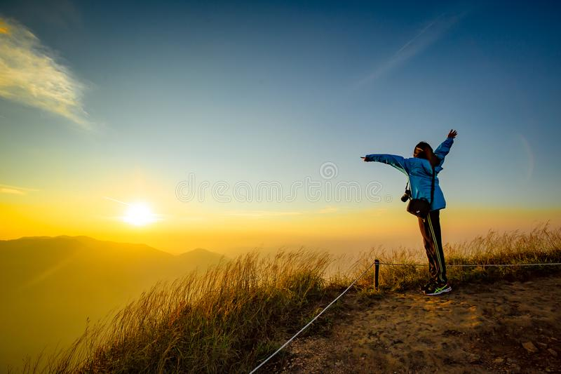 Lonely woman on top of the mountain with sunrise background stock image
