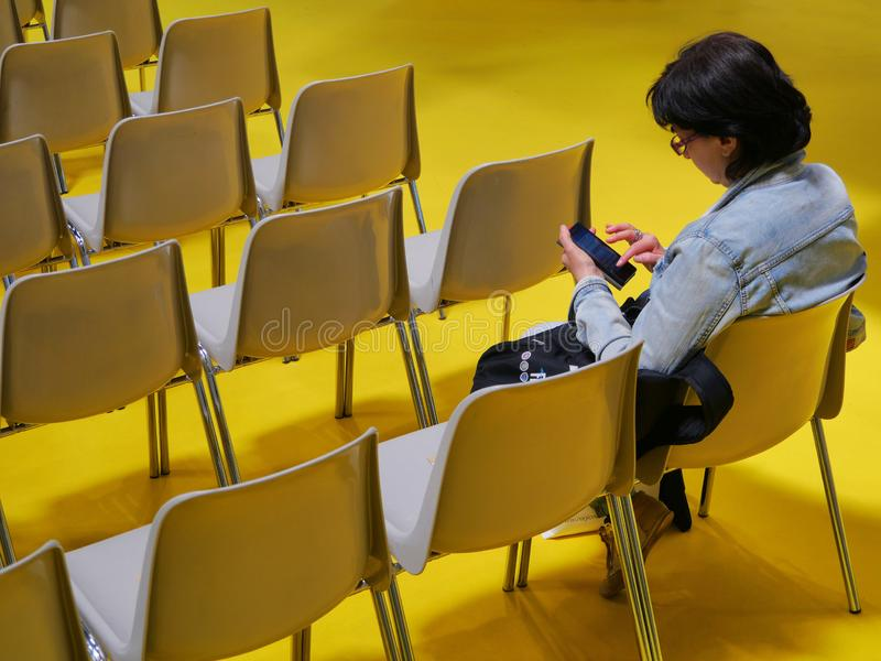 Lonely woman watching smartphone in empty seats room stock photo
