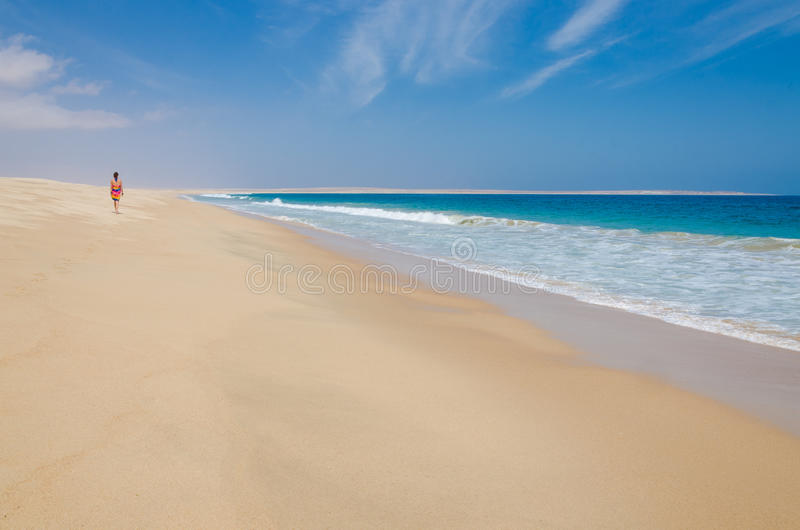 Lonely woman wearing colorful sarong walking along deserted beach stock photos