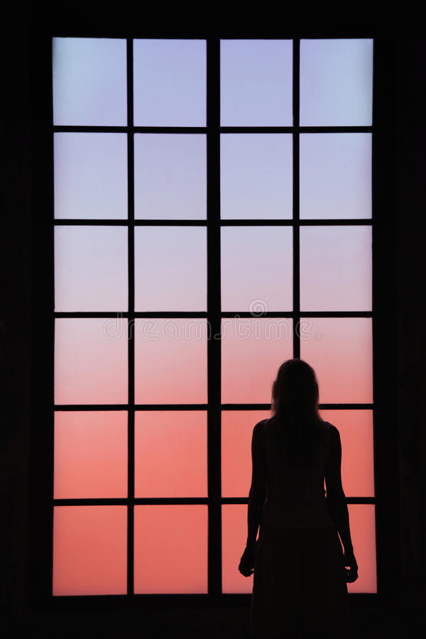 Lonely women looking through big closed glass window stock photography