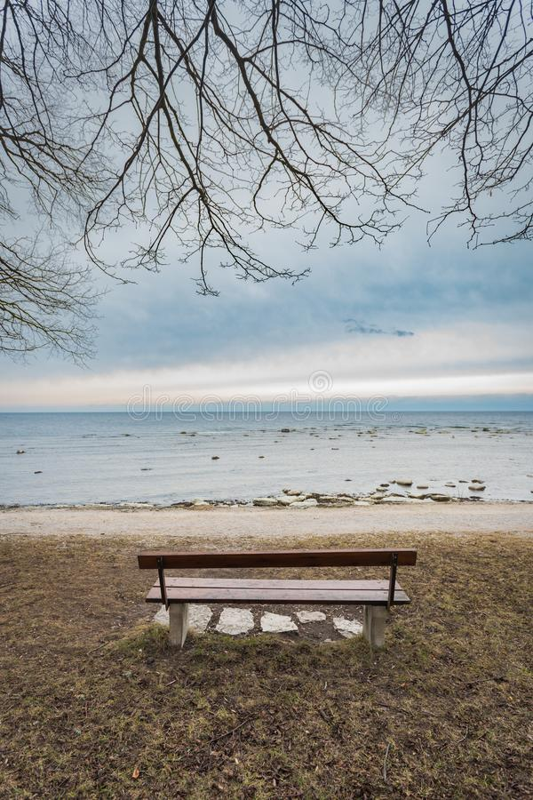 Lonely wooden bench on the autumn sea with cloudy sky. Picture of Lonely wooden bench on the autumn sea with cloudy sky, beach, landscape, nature, calm, blue royalty free stock image