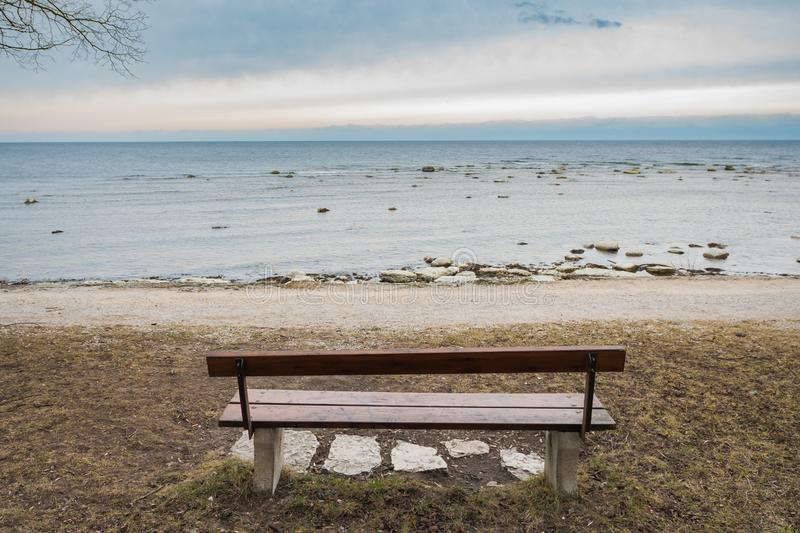 Lonely wooden bench on the autumn sea with cloudy sky. Picture of Lonely wooden bench on the autumn sea with cloudy sky, beach, landscape, nature, calm, blue royalty free stock photo