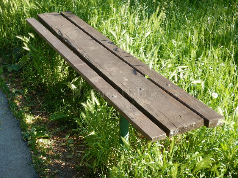 Lonely wooden bench in a high grass. A lonely wooden bench in a high grass royalty free stock images