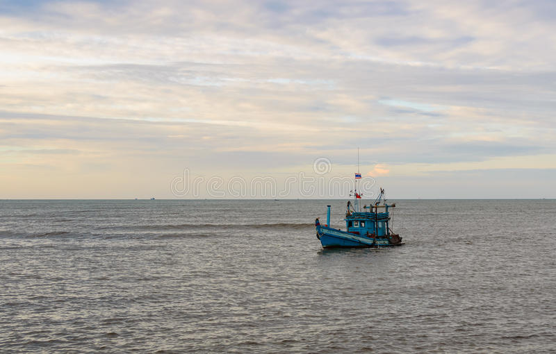 A lonely wooden fishing boat returns to the village after night catching at dawn royalty free stock photography