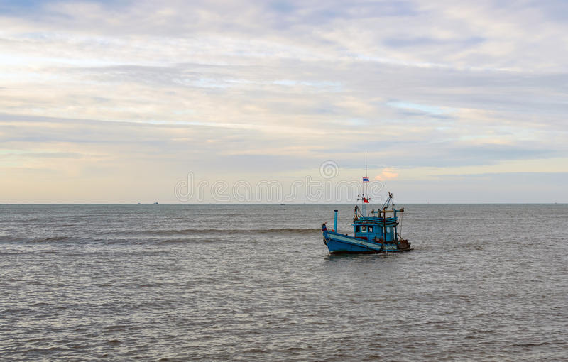 A lonely wooden fishing boat returns to the village after night catching at dawn stock photos