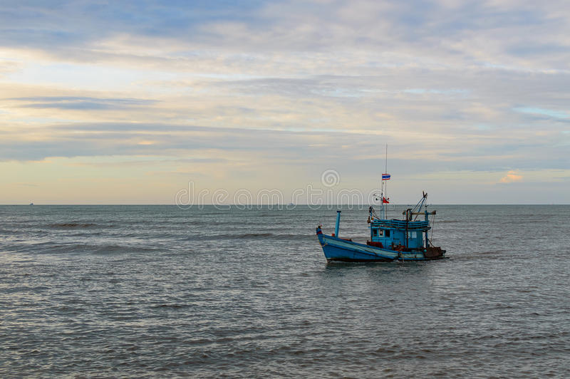 A lonely wooden fishing boat returns to the village after night catching at dawn royalty free stock photos