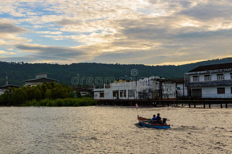 A lonely wooden fishing boat returns to the village after night catching at dawn stock image