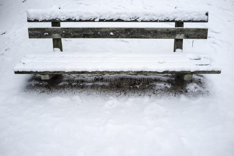 Park bench covered with fresh snow stock photo