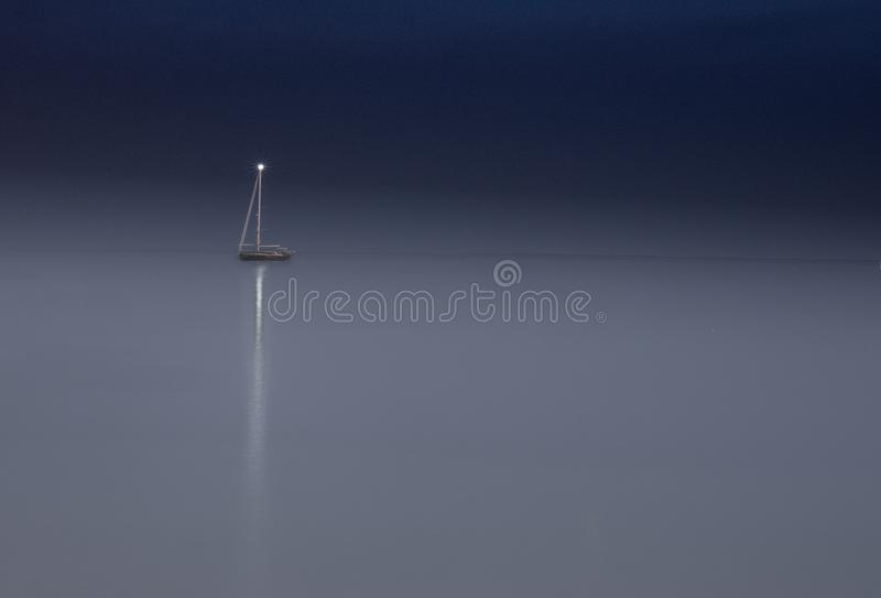 Lonely Yacht in the night. Yacht seaview light evening bluesky sunset bluewater horizon single sole desolate lonely fare away at night fog summer France royalty free stock photography
