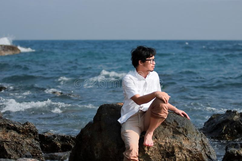 Lonely young Asian man sitting on the rock of sea shore royalty free stock photos