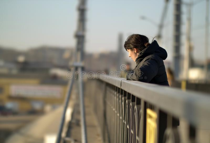 Lonely young brunette girl stands on the bridge on a sunny day royalty free stock photography