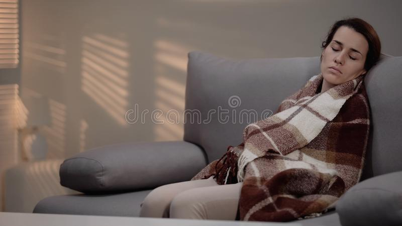 Lonely young depressed female sleeping on couch, covered with plaid, despair royalty free stock images