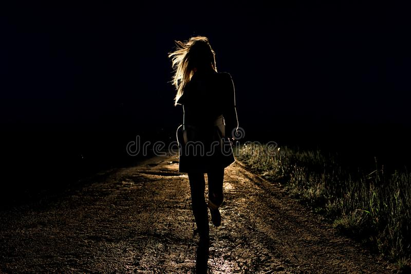 Lonely young frightened woman on an empty night road runs away in the light of the headlights of her car stock image
