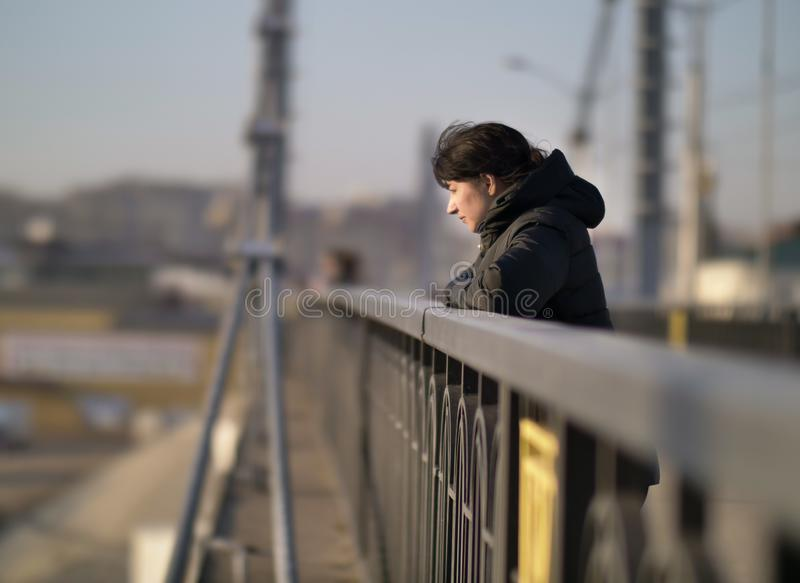 Lonely young girl stands on the bridge on a sunny day stock photo