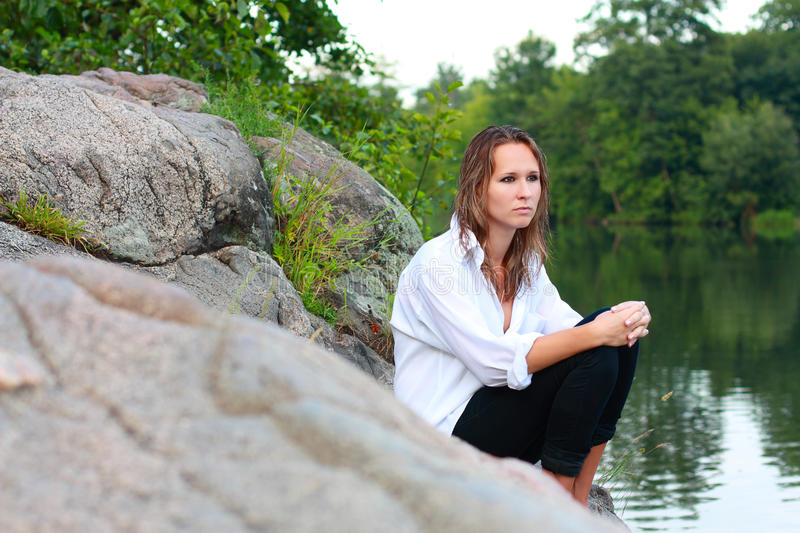 A lonely young woman sitting on rocks on the river stock images