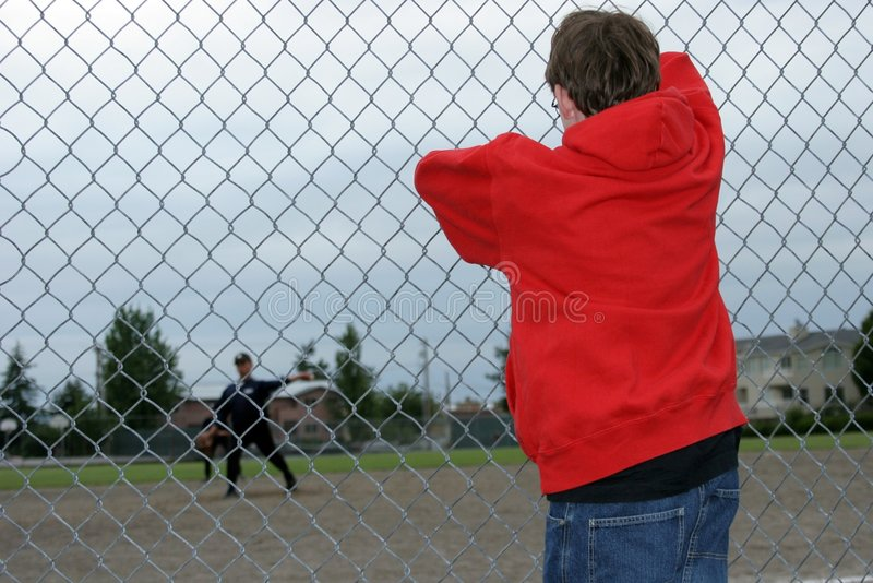 The Loner. A teenage boy looking in from the outside royalty free stock image