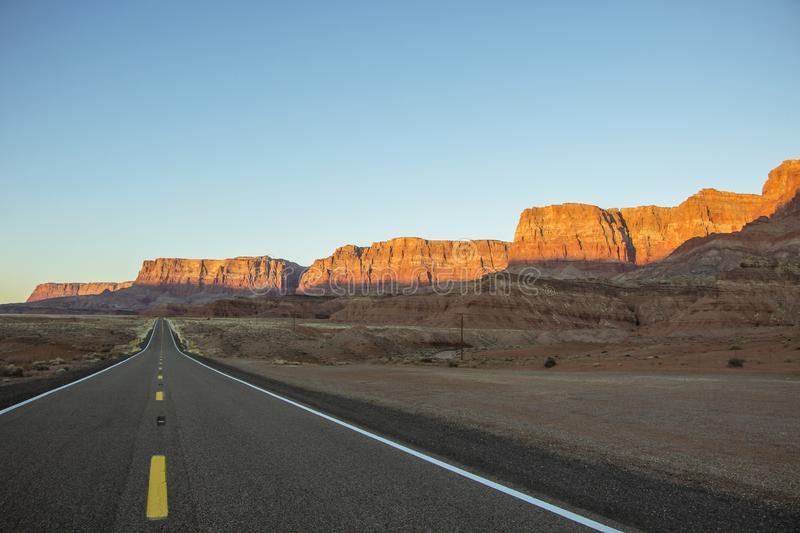 Lonesome high desert highway in the Southwest USA. Lonesome desert highway in the Southwest USA with stunning red rock cliffs in the background royalty free stock photography