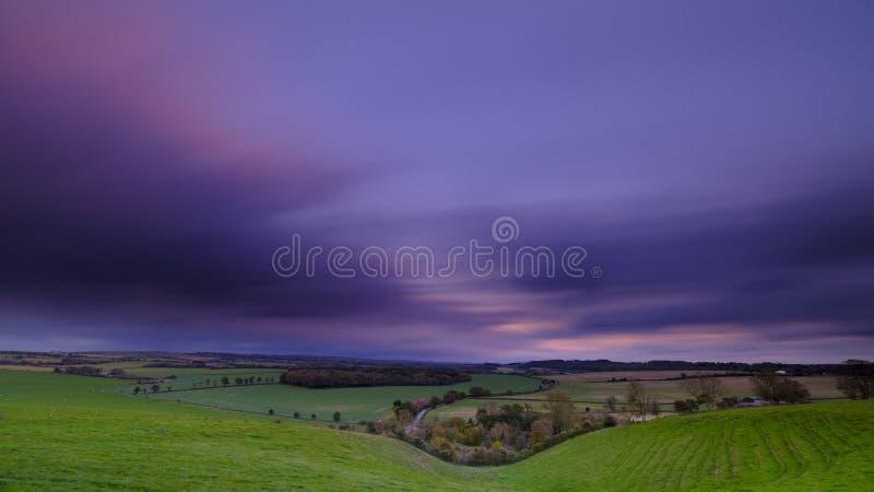Lonf五颜六色的秋天日落的快门速度在看往宽广的半便士铜币的Hambledon谷的下来,在边缘 图库摄影