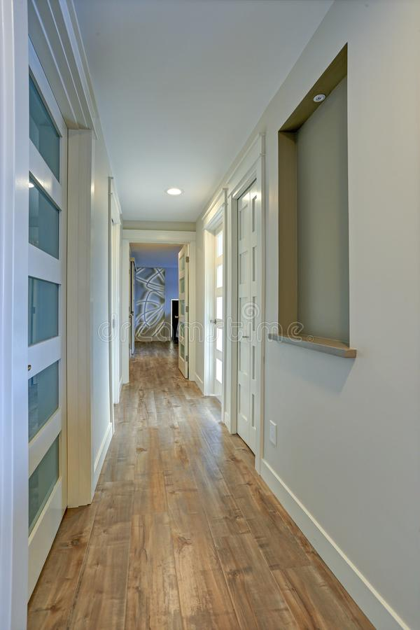 Long, étroit couloir avec les portes blanches accentuées avec les panneaux en verre photo libre de droits