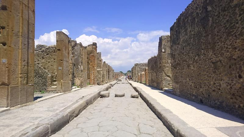 Long ancient road in Pompeii flanked by old walls disappearing to vanishing point in the distance with stone crossing royalty free stock photos