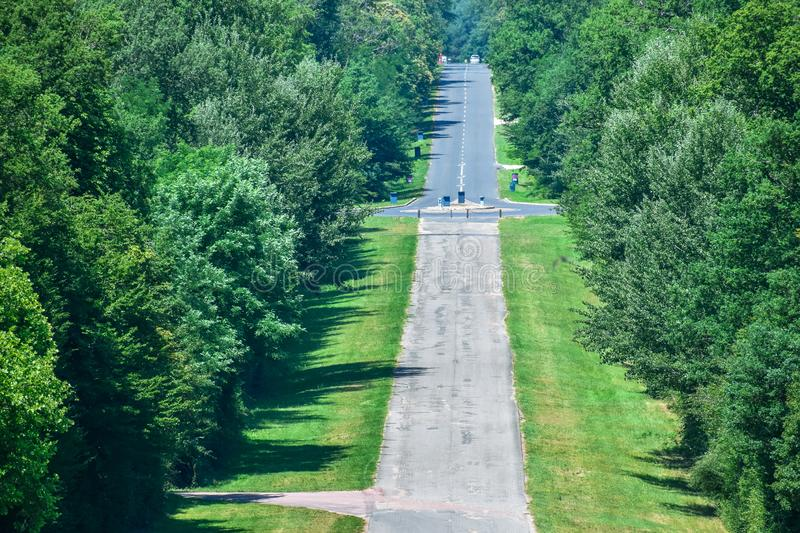 Long asphalt straight road through the forest. Road with ups and downs. Sunny and cloudy day royalty free stock image