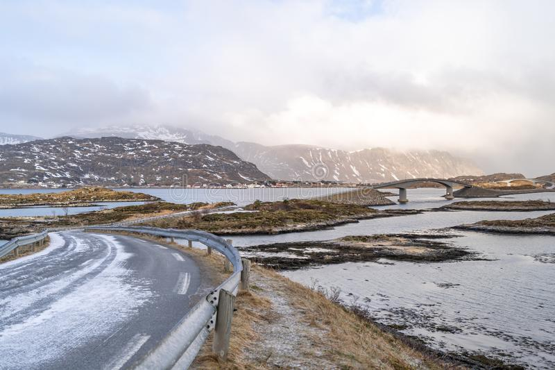 A long Atlantic Ocean winter Road and curved concrete bridge and water crossing from island in Lofoten. stock images