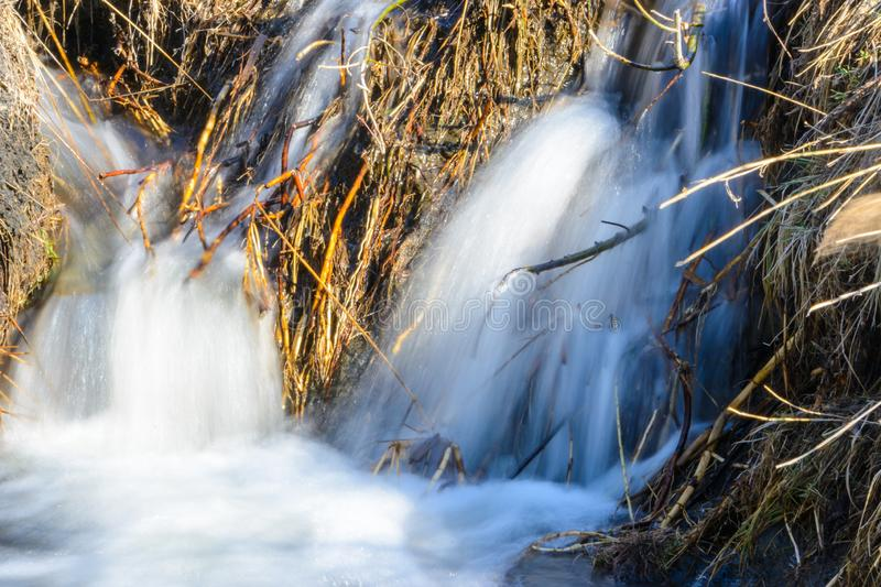 Long-awaited spring creeks flow over ravines and hills on a sunny day. Water rapids and waterfalls of streams among the dry grass stock image