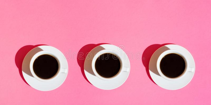 Long banner for cafes bars. White Cups of Coffee with Saucer on Neon Fuchsia Pink Color Background. Top View. Morning Breakfast Energy Caffeine Addiction royalty free stock images