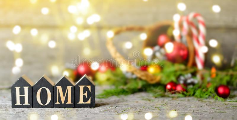 Long banner Christmas composition with and Shining lights. Red balls, Pine cones, lollipop, toy houses text Home on Wooden Table. Copy Space Drawing lights royalty free stock image