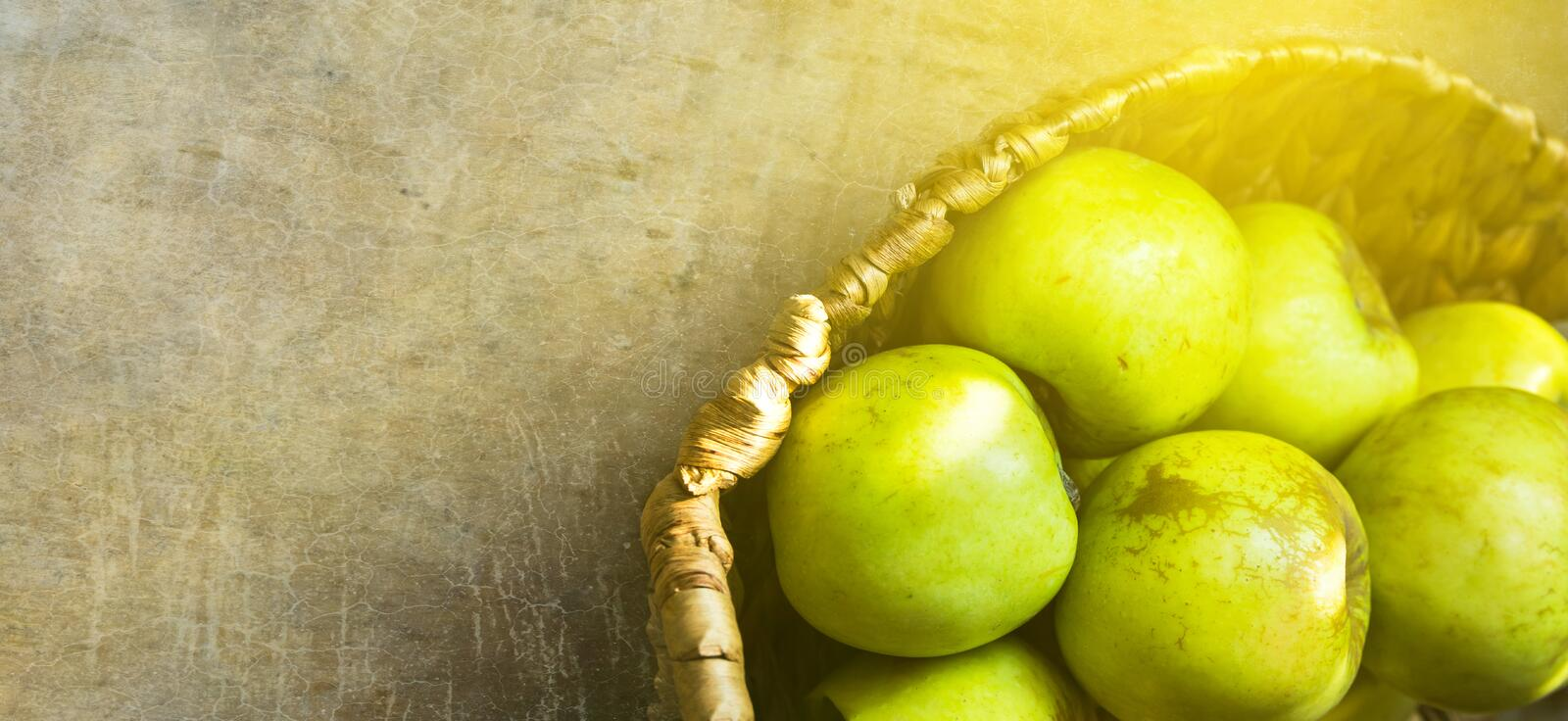 Long banner fresh green organic apples in wicker basket on rustic wooden table in golden sunlight. Local produce royalty free stock photography