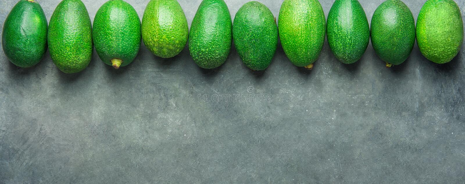 Long Banner Header. Bunch of Ripe Raw Avocados Arranged in Upper Border on Dark Stone Background. Top View Copy Space. Healthy. Lifestyle Vitamins Oil royalty free stock photography
